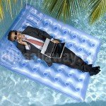 Aerial photograph of a man in a black suit and red tie, floating on a large blue raft in a pool. He is wearing sunglasses, talking on a cellphone, and using a laptop that sits in his lap. There are palm tree branches overhead. The blog is about floating offices on superyachts, so the photo ties into the water theme.