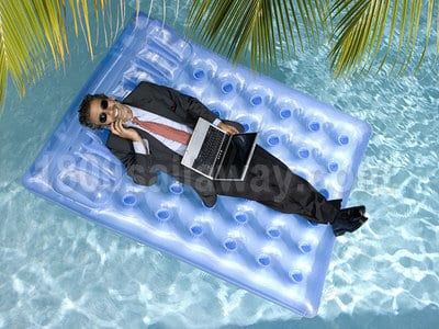 Aerial photograph of a man in a black suit and red tie, floating on a large blue raft in a pool. He is wearing sunglasses, talking on a cellphone, and using a laptop that sits in his lap. There are palm tree branches overhead.