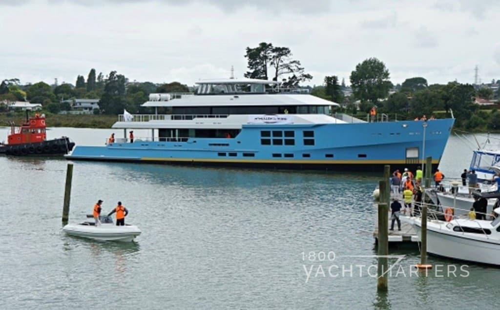 Photo of yacht charter boat with light blue hull.  She is being pushed into the marina by a red tugboat. People stand on a dock and watch.