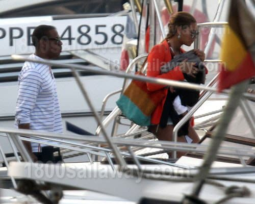 Photograph of Beyonce and Jay-Z boarding a yacht for a vacation. She is wearing a red shirt. He is wearing a white shirt and dark shorts.