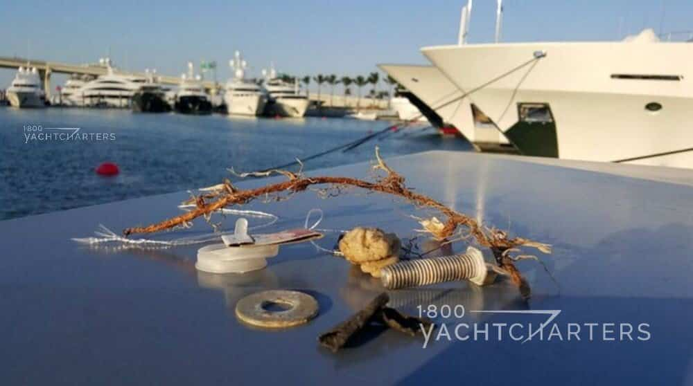 Miscellaneous trash items found on dock of yacht marina laid out on the top of a metal dock box