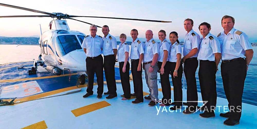 Superyacht crew stands in a line. They are all wearing pants and white shirts with epilettes. They are standing on the deck of a yacht. There is a helicopter in the background.