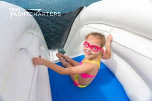 Smiling little girl ready to go down inflatable slide from the top of a yacht