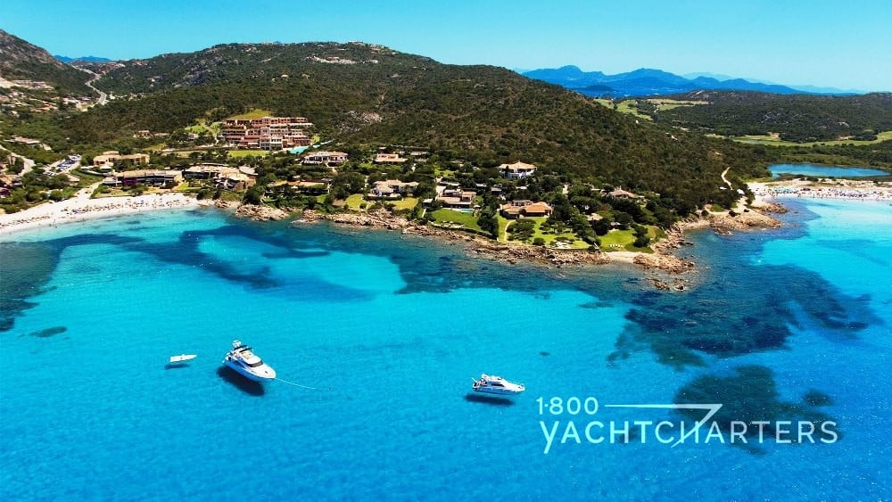 Sardinia photo of island with yachts anchored in turquoise water in front of it