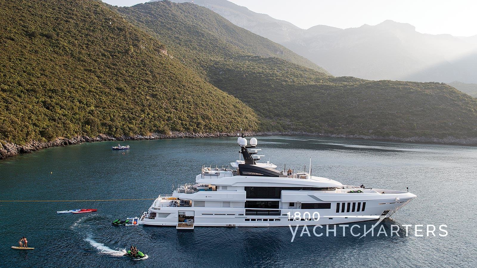 Profile photograph of a yacht at anchor in a quiet harbor.  There are mountains covered in mist in the background. The yacht is facing the right side of the photograph.  There is a jetski zipping around in the water at the back of the yacht.