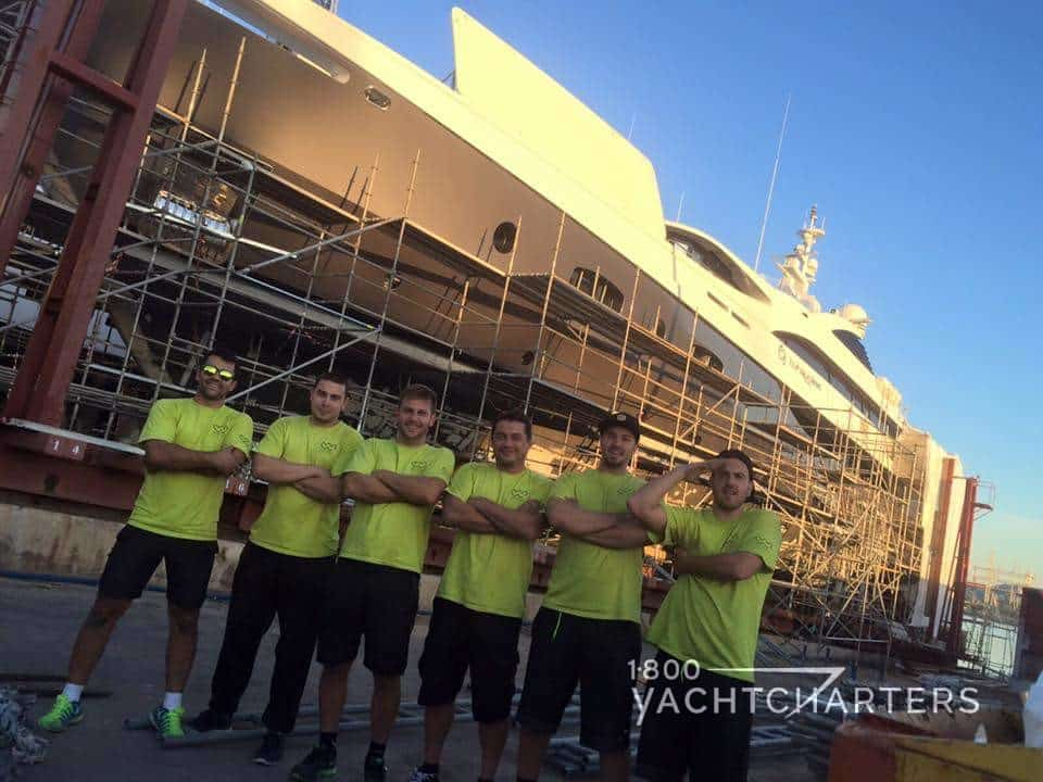 Wild Boys superyacht team stand in front of latest project