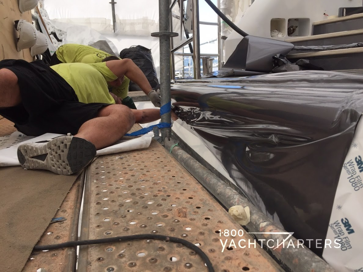 worker lays on dock and applies paint wrap to the side of a yacht