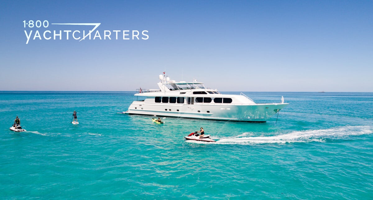 Photograph of white boat at anchor with jetskis zooming around in front of it. The yacht is facing the right side of the photo. The water is turquoise. The sky is blue and cloudless. The sun is shining