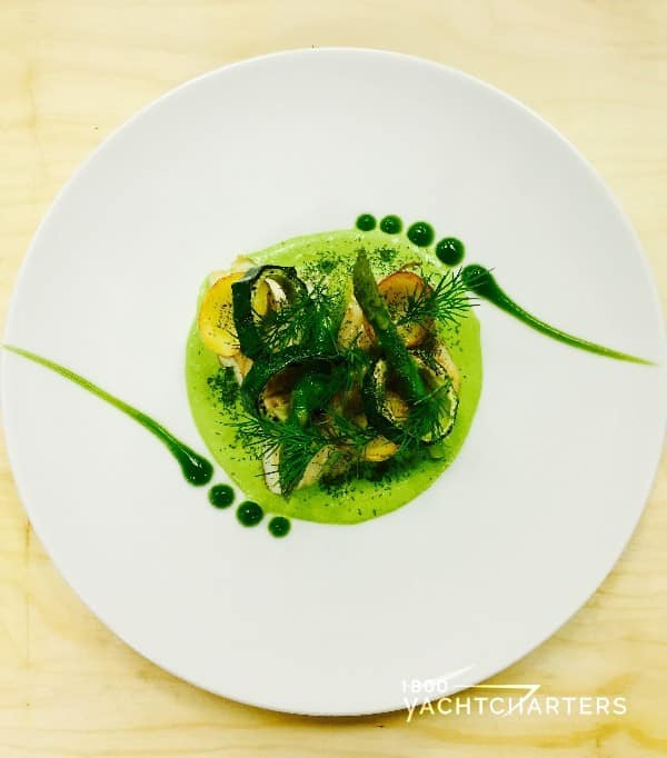Round white plate with asparagus puree with sea bass and courgette garnish
