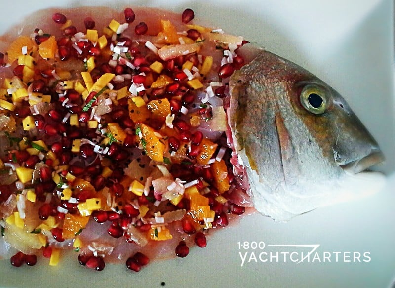 sea bass with pomegranate, red onion, and mango salsa on a white plate