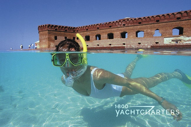 Girl in white bathingsuit wearing mask and yellow snorkel and snorkeling in front of a caribbean fort