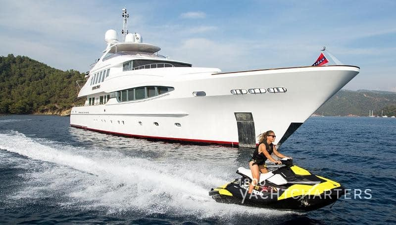 Seven Sins motoryacht at anchor with woman on yellow jetski riding by the yacht's bow