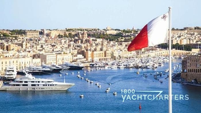Yacht marina in Malta with superyacht in foreground and Maltese flag flying above marina