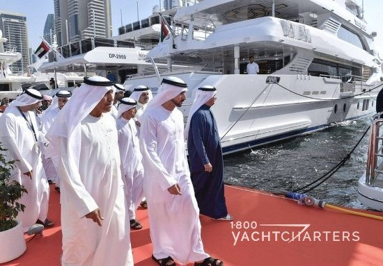 Sheiks in white gowns (and 1 in a blue gown) walking red carpet between yachts at Dubai International Boat Show