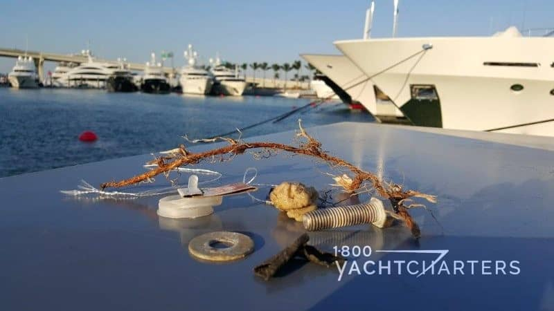 Photograph of various pieces of debris picked up on dock in a marina. Items include a metal washer, piece of rope, a silver bolt, a length of fishing line, and a piece of plastic. The background of the photo shows multiple superyachts docked, with palm trees in the background.