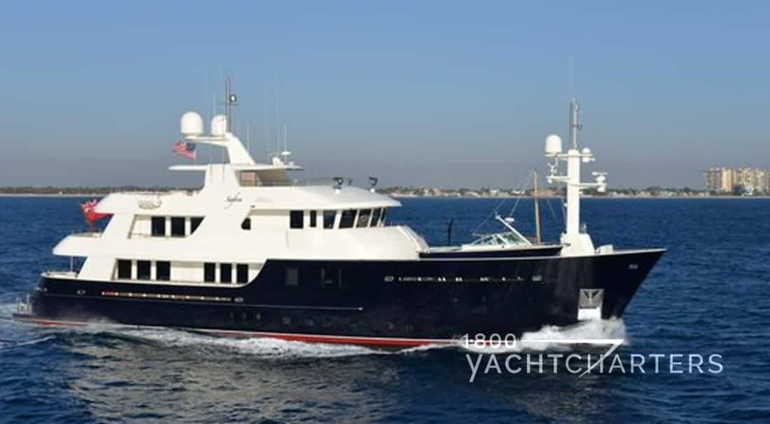 Photograph of motoryacht Safira running. Dark blue hull. White superstructure. Waves lapping at bottom of yacht