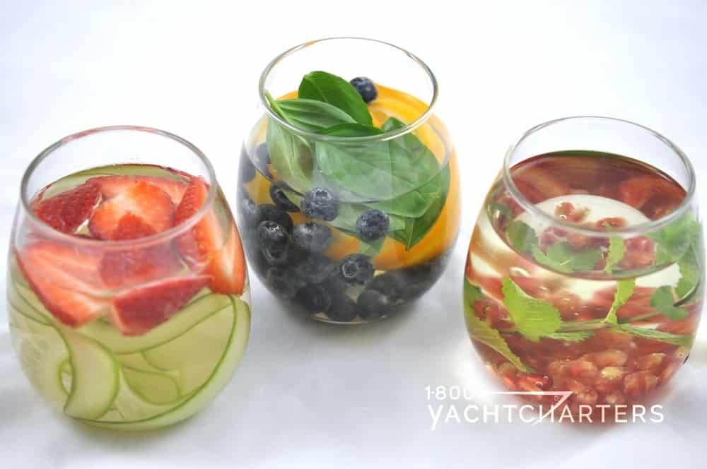 three round glasses containing water infused with strawberries blueberries pomegranate orange cucumber
