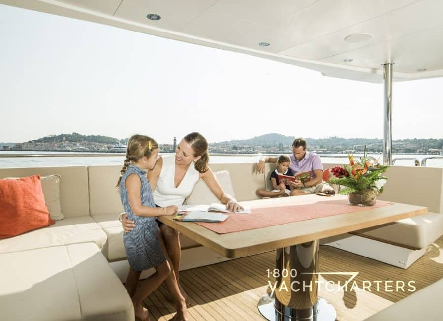 AQUA LIBRA motoryacht aft deck with young mother speaking to little girl and young father reading to little boy