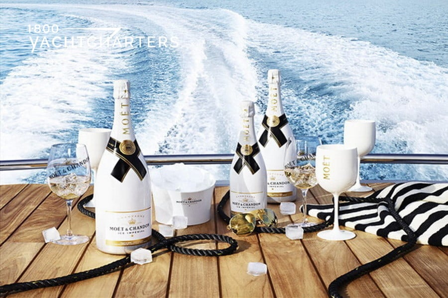multiple white bottles of Moet Ice Imperial champagne sitting on the back of a yacht with running waves in the background