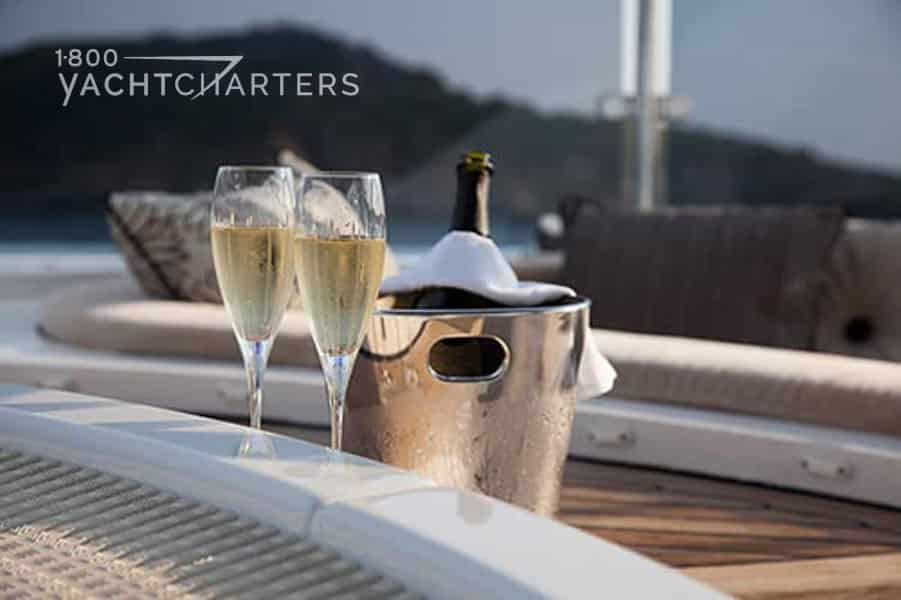 champagne in ice bucket next to full champagne flutes next to the ondeck jacuzzi of a yacht