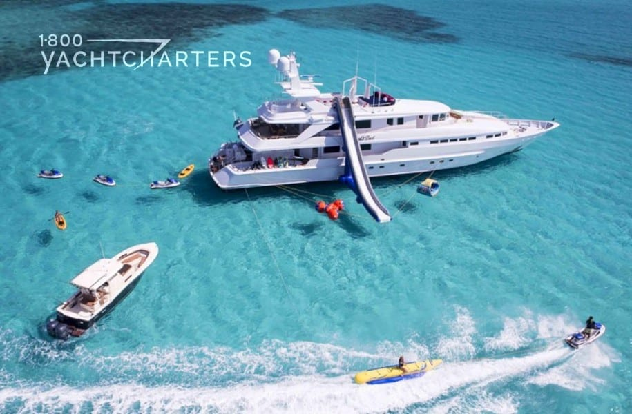 luxury yacht charter boat at anchor with inflatable slide from top deck to water, and guests on watertoys surrounding the yacht