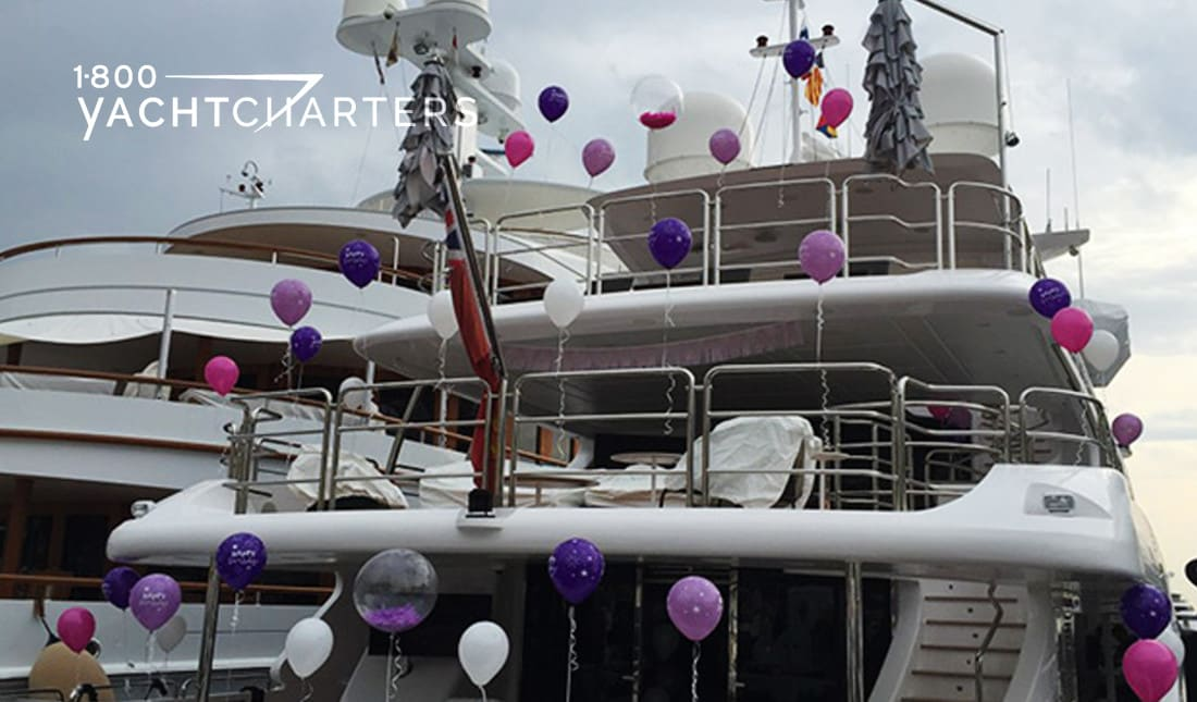 The back of a yacht at dock tied with pink and purple balloons