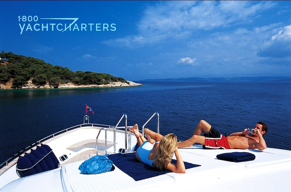 A couple relaxing on the bow of a yacht with a private island off in the distan...</p> 							<a href=