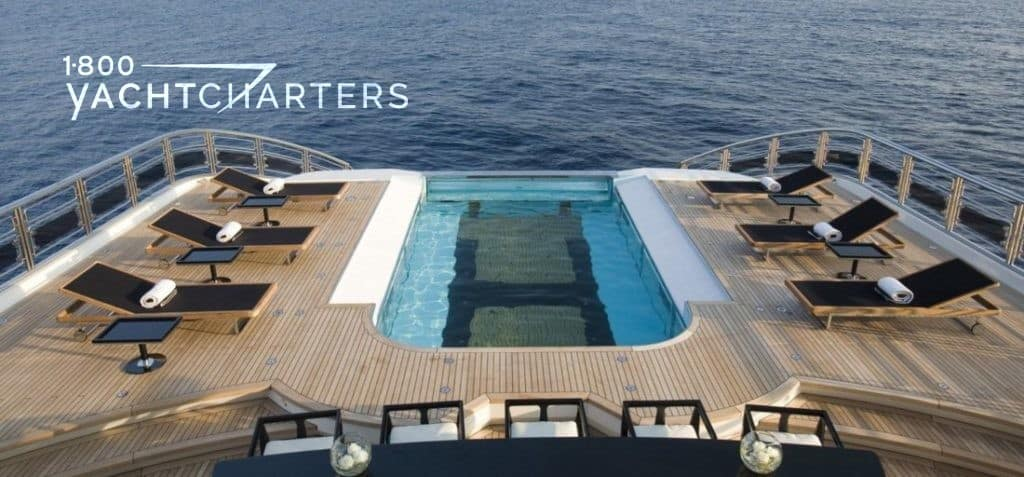Deck view with swimming pool with H for helipad on the bottom of it, surrounded by sunloungers on the back of a luxury yacht