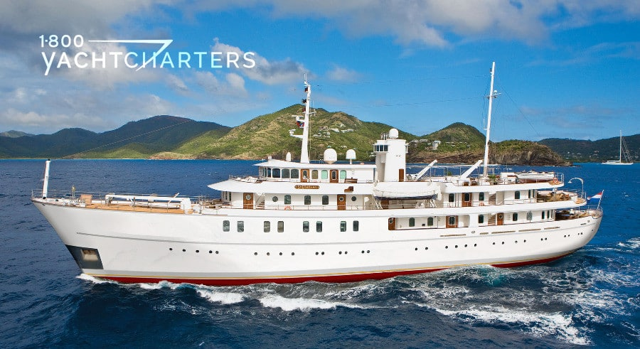 Sherakhan motoryacht profile with white hull and superstructure and caribbean mountain in background