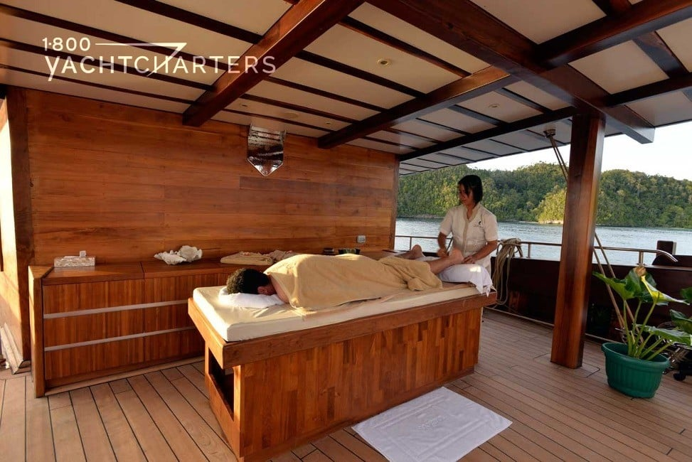 masseuse giving massage to person on massage bed on deck of sailboat Lamima