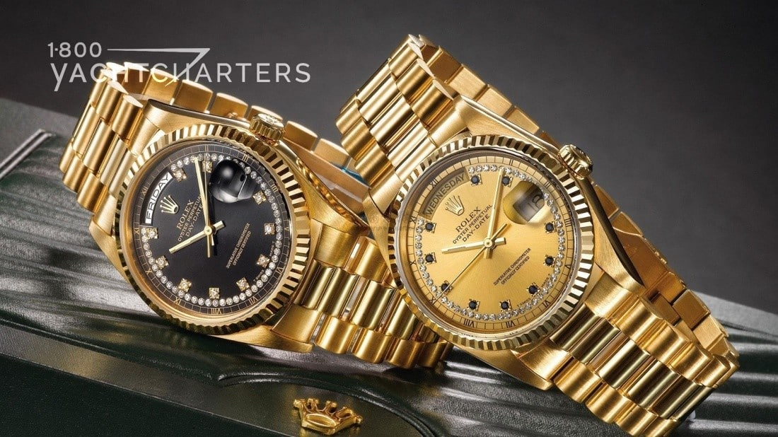 Two gold watches. The left one has a black face. The right one has a gold face. Both have gold metal wristbands.