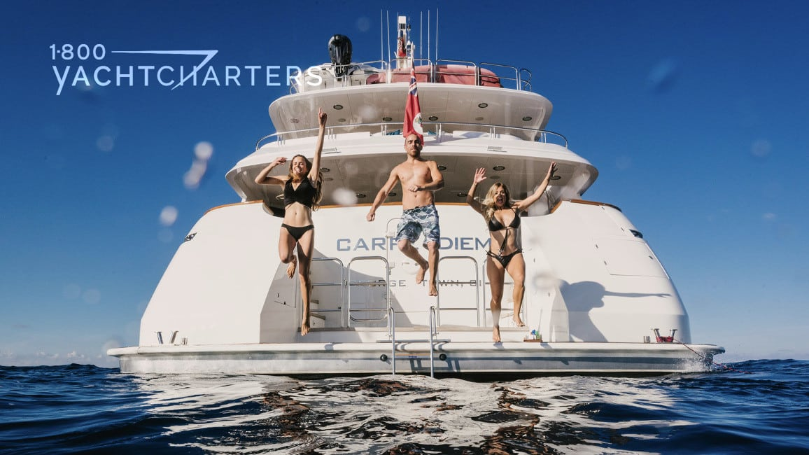 Three adults jumping into the water off of the swim platform of yacht CARPE DIEM