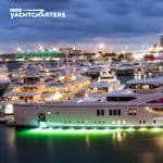 Sunset photo of dock of superyachts at Miami Yacht Show with underwater lighting under each yacht