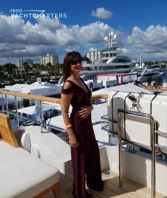 Jana Sheeder, President of 1-800 Yacht Charters, stands on superyacht deck at yacht show