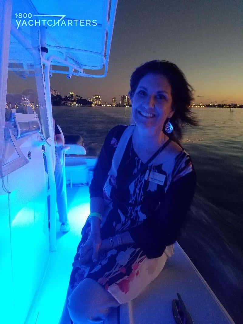 Jana Sheeder leans on side of Jupiter yacht as it races along Miami skyline at sunset