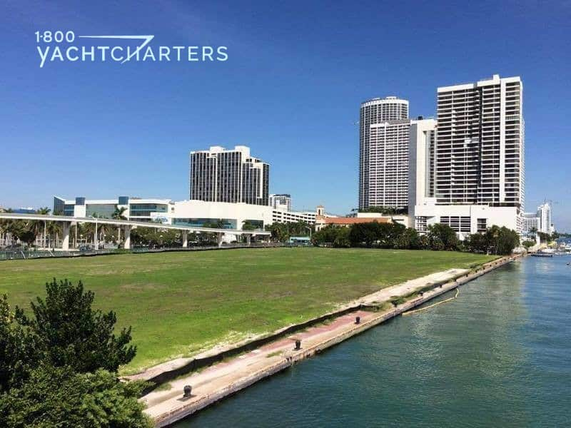 Photograph of Miami Yacht Show future site - green grass with seawall in downtown Miami with highrises in the background