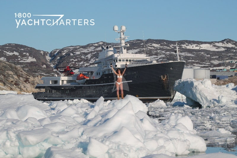 Woman in white bikini and arms raised in air standing on snow in front of motoryacht LEGEND