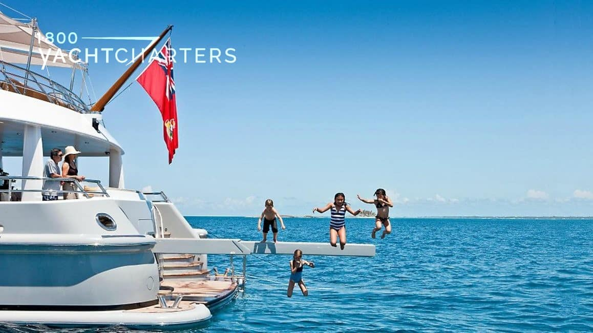 Four children jumping off of a diving board at the back of a superyacht while parents look on from the back of the boat