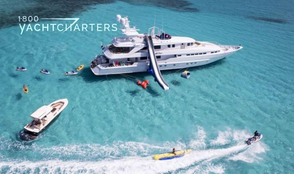 Aerial photo of yacht at anchor with an inflatable slide coming down from the top deck. Multiple jetskis and tenders are racing around in the water around the boat. The water is clear and turquoise.