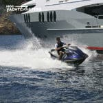 Photograph of young man on waverunner racing by the side of motoryacht ZOOM ZOOM ZOOM. The yacht is facing the upper left side of the photo. The waverunner is headed toward the center right side of the photo.