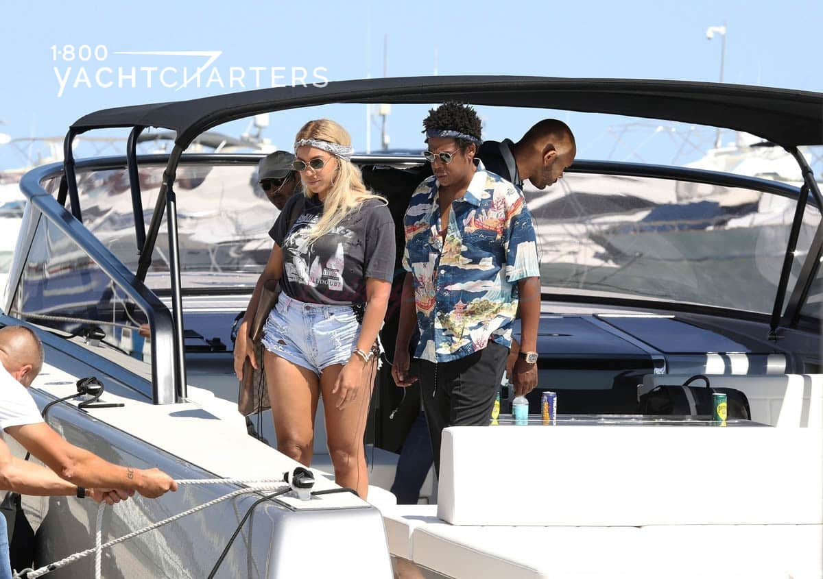 Photograph of Beyonce and Jay-Z waiting for person to tie ropes to the boat from the dock. Captain of boat is pictured behind the couple.
