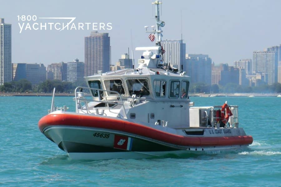 Photo of US Coast Guard boat on Biscayne Bay with Miami Florida skyline in background. Sunny day.