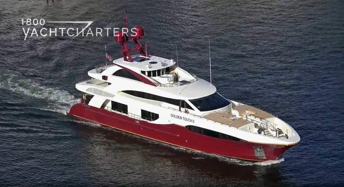 Aerial photograph of motoryacht Golden Touch II. Red hull and white superstructure with red satellites on top of yacht.
