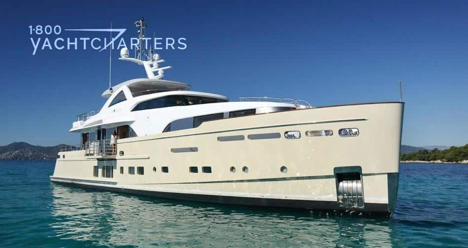 Photograph of motoryacht SOLIS at quarter profile. Hull is beige. Superstructure is white. Yacht is at anchor.
