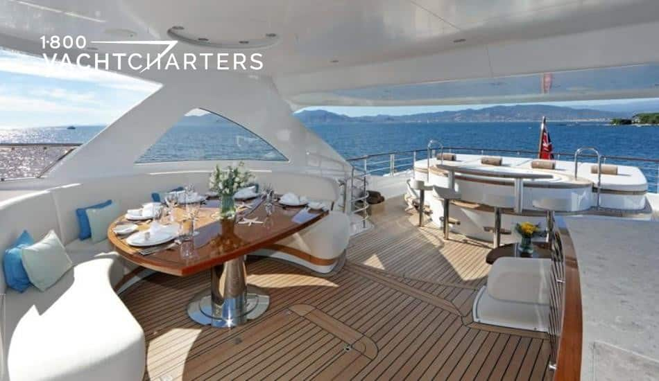 Photograph of the top deck of a motoryacht that has a hot tub and dining table.