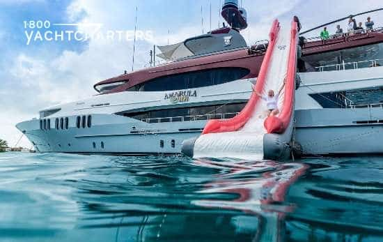 Photograph of a girl sliding down the inflatable red and white slide of motoryacht Amarula Sun. The yacht is red and white, and the slide matches.