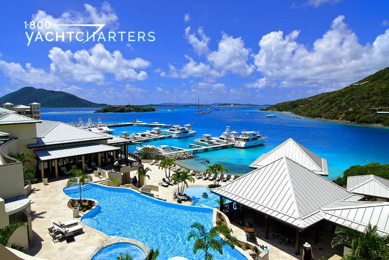 Aerial photo of Scrub Island Resort Spa and Marina. Photo shows a blue swimming pool amid beige buildings with shiny metal roofs. There is a marina with boats in the background, and mountains on either side of the back of the photo. The ocean water is deep blue. The sky is blue and full of puffy white clouds.