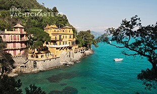 Photograph of Argentario Italy. The water is turquoise, and there are homes built above a solid rock foundation