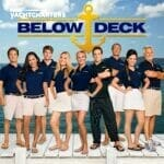 Photograph of 9 members of the Below Deck television series. Everyone is standing with their hands on their hips. All are white shorts or skirts and navy blue shirts. The chef in the photo is wearing all black. The words, Below Deck, with a yellow anchor (the Below Deck logo) is above the crew members. The background of the photo is blue sky and white puffy clouds
