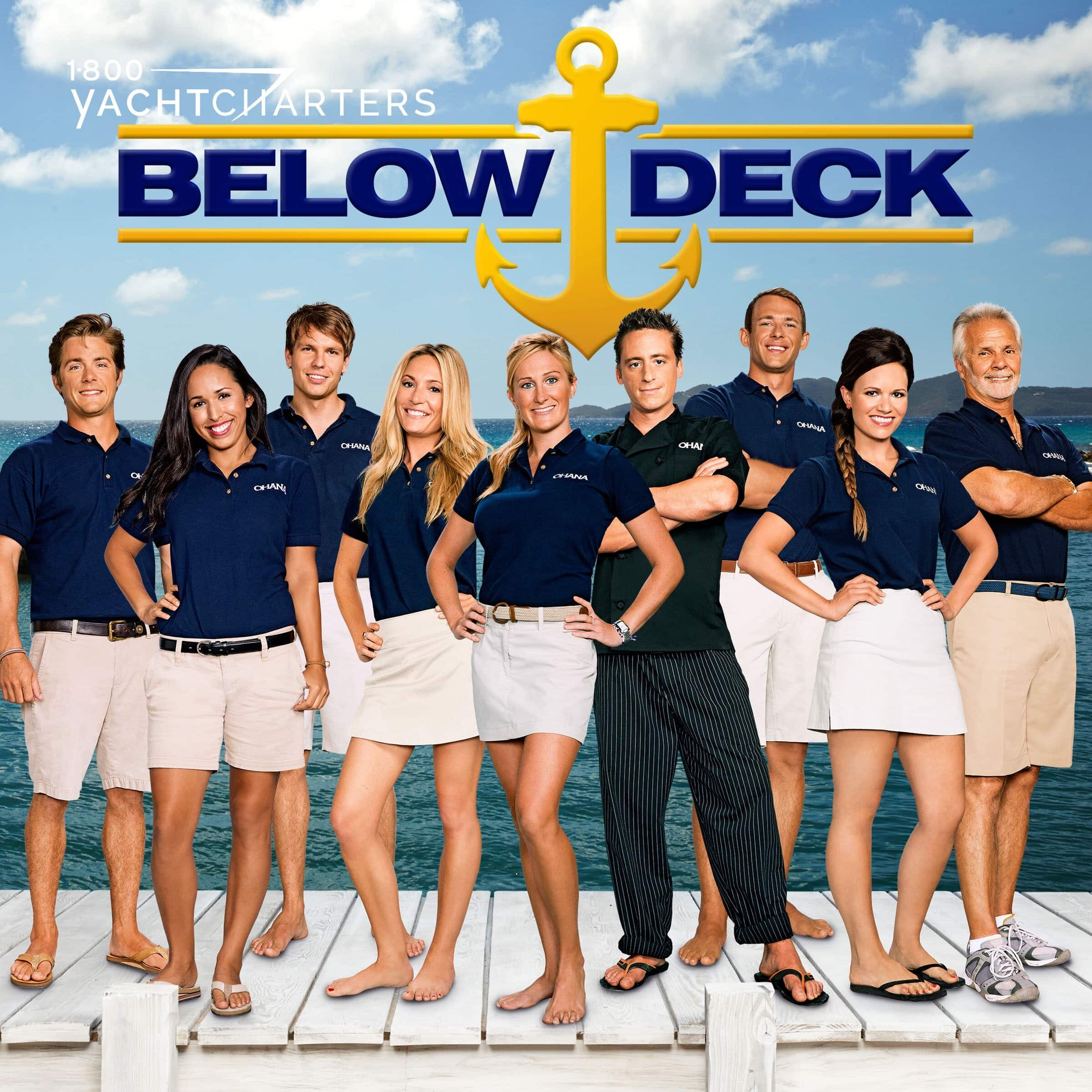 Photograph of 9 members of the Below Deck television series. Everyone is standing with their hands on their hips. All are white or khaki shorts or skirts and navy blue shirts. The chef in the photo is wearing all black. The words, Below Deck, with a yellow anchor (the Below Deck logo) is above the crew members. The background of the photo is blue sky and white puffy clouds